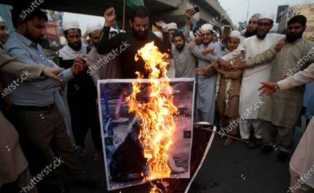 People burn a picture of French President Macron during a demonstration against French President Macron's comments over Prophet Muhammad caricatures, outside the French consulate in Lahore, Pakistan, 28 October 2020. A group of protesters gathered to protest against Macron's comments following the recent beheading of a teacher in France, after he had shown caricatures of the Prophet Muhammad in class. Pakistani Prime Minister Imran Khan, had also accused Macron of attacking and hurting the sentiments of millions of Muslims in Europe and across the world.