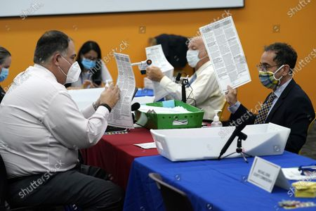 Attorney Nathaniel Klitsberg, left, and Judge Ken Gottlieb, right, examine ballots that could not be read by scanning machines during a meeting of the Canvassing Board at the Broward County Voting Equipment Center, in Lauderhill, Fla
