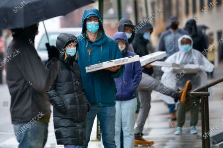 Voters hold boxes of pizza distributed free by a local pizza company while waiting in line in the rain to cast their absentee ballots, in Portland, Maine. Pizzaiolo, a local pizzeria specializing in New York-style pizza, gave out pizzas in support of early votingstockképe