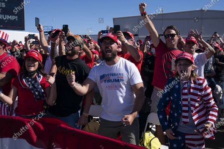 Supporters of President Donald Trump cheer as he arrives for a campaign rally at Laughlin/Bullhead International Airport, in Bullhead City, Ariz