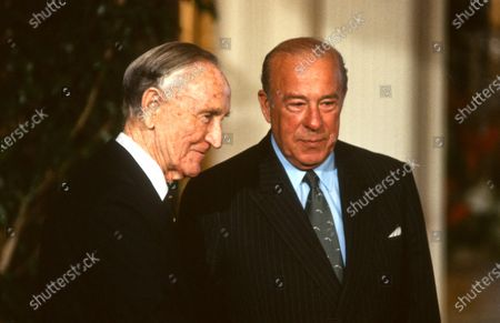 Former United States Senate Majority Leader and former US Ambassador to Japan Mike Mansfield, left, and US Secretary of State George Shultz, right, after they accepted the Medal of Freedom from US President Ronald Reagan first lady Nancy Reagan at the White House in Washington, DC.