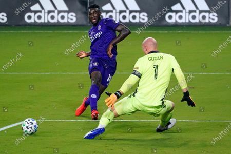 Stock Image of Orlando City forward Daryl Dike, left, takes a shot on goal but misses as Atlanta United goalkeeper Brad Guzan (1) defends during the first half of an MLS soccer match, in Orlando, Fla