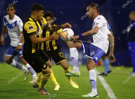Giovanni Gonzalez of Uruguay's Penarol, left, and Andres Manuel of Argentina's Velez Sarsfield, fight for the ball during their Copa Sudamericana soccer match in Buenos Aires, Argentina