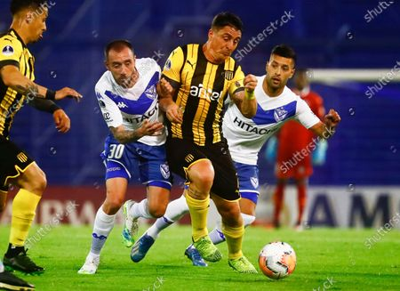 Cristian Rodriguez of Uruguay's Penarol, center, battles for the ball with Andres Manuel, left, and Ezequiel Janson, both of Argentina's Velez Sarsfield, during their Copa Sudamericana soccer match in Buenos Aires, Argentina