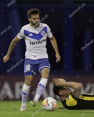 Cristian Rodriguez of Uruguay's Penarol, right, reacts after being fouled by Agustin Bouzat of Argentina's Velez Sarsfield, during their Copa Sudamericana soccer match in Buenos Aires, Argentina