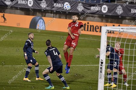 Toronto FC's Omar Gonzalez controls the ball as New York City FC's Ronald Matarrita, left, and Maxime Chanot, center, watch during the second half of an MLS soccer match, in East Hartford, Conn