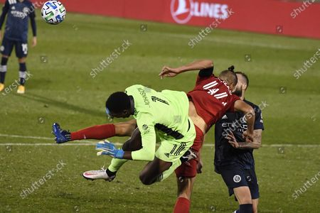 New York City FC goalkeeper Sean Johnson, left, and Toronto FC's Omar Gonzalez collide during the second half of an MLS soccer match, in East Hartford, Conn