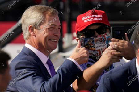 Nigel Farage, left, a former member of the European Parliament representing the UK and member of the Brexit Party, poses for a picture with a supporter of President Donald Trump prior to Trump arriving for a campaign rally at Phoenix Goodyear Airport, in Goodyear, Ariz