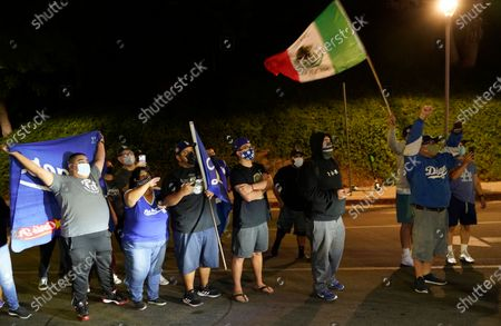 Los Angeles Dodgers fans cheer for pitcher Julio Urías as he drives away from Dodger Stadium in Los Angeles on Wednesday night, after the Dodgers returned from Arlington, Texas, where they defeated the Tampa Bay Rays in the baseball World Series