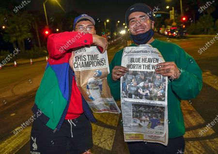 Los Angeles Dodgers fans hold up local newspapers while looking for autographs from players departing Dodger Stadium in Los Angeles on Wednesday night, after the Dodgers returned from Arlington, Texas, where they defeated the Tampa Bay Rays in the baseball World Series