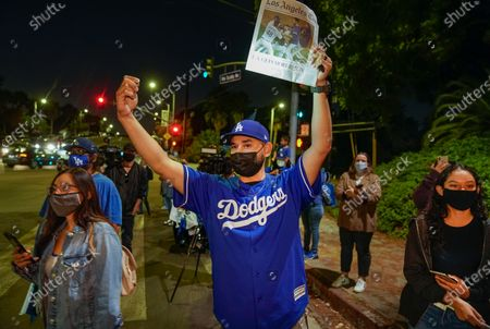 Los Angeles Dodgers fan Douglas Magana holds a copy of Los Angeles Times while looking for autographs from players leaving Dodger Stadium in Los Angeles on Wednesday night, after the Dodgers returned from Arlington, Texas, where they defeated the Tampa Bay Rays in the baseball World Series