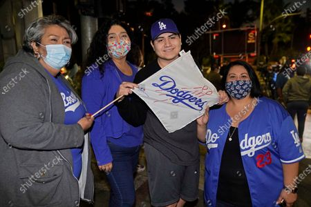 Los Angeles Dodgers fan Lydia Vargas, 70, left, and her family from East Los Angeles wait to see players arrive at Dodger Stadium in Los Angeles on Wednesday night, . Vargas wore her Clayton Kershaw T-shirt and blue tennis shoes to work before heading over to Chavez Ravine with her daughters and 19-year-old grandson. She watched the buses of team members roll by. The Dodgers defeated the Tampa Bay Rays in the baseball World Series in Arlington, Texas