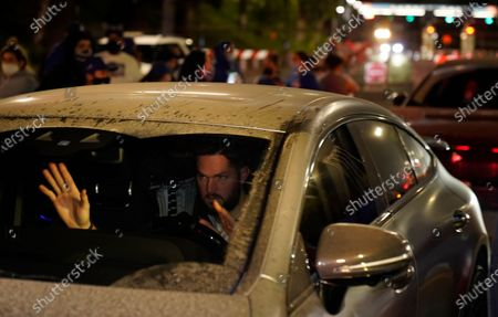 Los Angeles Dodgers pitcher Alex Wood waves to fans as he drives away from Dodger Stadium in Los Angeles, after the Dodgers returned to Los Angeles following their win over the Tampa Bay Rays in the baseball World Series in Arlington, Texas