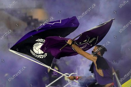 Orlando City fans wave flags and set off smoke bombs during the first half of an MLS soccer match between Orlando City and Atlanta United, in Orlando, Fla