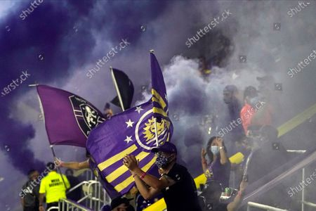 Fans cheers after setting off smoke bombs after Orlando City scored against Atlanta United during the first half of an MLS soccer match, in Orlando, Fla