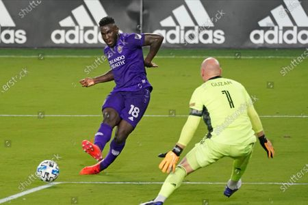 Orlando City forward Daryl Dike, left, takes a shot on goal but misses as Atlanta United goalkeeper Brad Guzan (1) tries to defend during the first half of an MLS soccer match, in Orlando, Fla