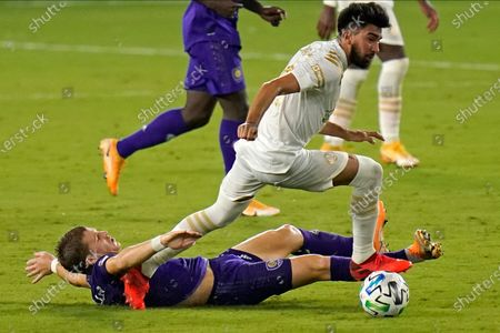 Atlanta United midfielder Marcelino Moreno, right, moves the ball past Orlando City forward Chris Mueller,lower left, during the second half of an MLS soccer match, in Orlando, Fla
