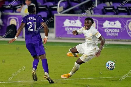 Orlando City midfielder Andres Perea (21) and Atlanta United defender George Bello, right, battle for possession of the ball during the second half of an MLS soccer match, in Orlando, Fla