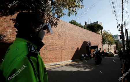 South Korean police officer stands outside a residence of former President Lee Myung-bak in Seoul, South Korea, . South Korea's top court upheld a 17-year sentence imposed on former President Lee Myung-bak for a range of corruption crimes in a final ruling Thursday that will send him back to prison