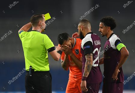 Referee Andreas Ekberg, left, books Basaksehir's Mehmet Topal, center, with a yellow card, during the Champions League group H soccer match between Basaksehir and Paris Saint Germain in Istanbul, . Paris Saint Germain won the match 2-0