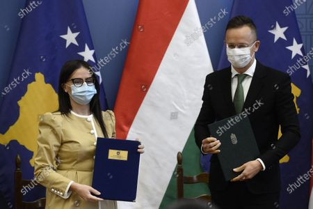 Stock Picture of Kosovar Minister of Foreign Affairs and Diaspora Meliza Haradinaj-Stublla (L) and Hungarian Minister of Foreign Affairs and Trade Peter Szijjarto (R) pose with documents after they signed an agreement on investment incentive and mutual investment protection in the latter's office in Budapest, Hungary, 29 October 2020.
