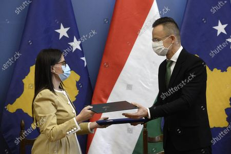 Kosovar Minister of Foreign Affairs and Diaspora Meliza Haradinaj-Stublla (L) and Hungarian Minister of Foreign Affairs and Trade Peter Szijjarto exchange documents after they signed an agreement on investment incentive and mutual investment protection in the latter's office in Budapest, Hungary, 29 October 2020.