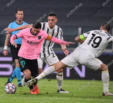Stock Photo of Juventus' Leonardo Bonucci (1st R), Merih Demiral (2nd R) defend Barcelona's Lionel Messi during the UEFA Champions League Group G match between Juventus and Barcelona in Turin, Italy, Oct. 28, 2020.