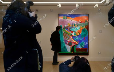David Hockney painting entitled 'Nichols Canyon' at Phillips auction house is viewed through the window in London, . The painting will be sold at auction on Dec. 7, in New York with an estimates value of US$ 35 million