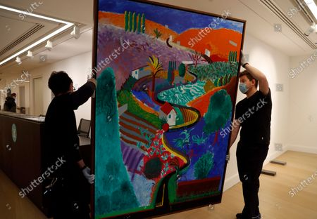 Two members of staff pose for the media next to a painting by David Hockney entitled 'Nichols Canyon' at Phillips auction house in London, . The painting will be sold at auction on Dec. 7, in New York with an estimates value of US$ 35 million