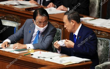 Japanese Prime Minister Yoshihide Suga (R) chats with Finance Minister Taro Aso (L) at Lower House's plenary session at the National Diet in Tokyo on Thursday, October 29, 2020. Suga delivered his first policy speech at the Diet on October 26.