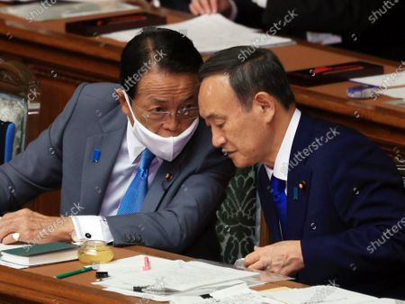 Japanese Prime Minister Yoshihide Suga (R) listens to Finance Minister Taro Aso (L) at Lower House's plenary session at the National Diet in Tokyo on Thursday, October 29, 2020. Suga delivered his first policy speech at the Diet on October 26.