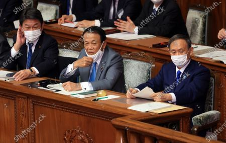 L) Japanese Prime Minister Yoshihide Suga, Finance Minister Taro Aso and Foreign Minister Toshimitsu Motegi listen to questions at Lower House's plenary session at the National Diet in Tokyo on Thursday, October 29, 2020. Suga delivered his first policy speech at the Diet on October 26.