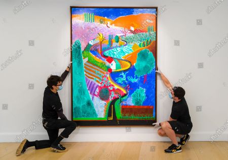 Two gallery technicians pose with a painting entitled 'Nichols Canyon' by artist David Hockney at Phillips auction house in Berkley Square, London, Britain, 29 October 2020. Nichols Canyon is David Hockney's first mature landscape and is expected to sell for $35m at auction.