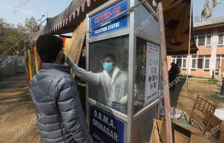A health worker takes a smaple from a person for a COVID-19 test in Srinagar, India, 29 October 2020. According media reports, India has the second-highest number of COVID-19 infections.