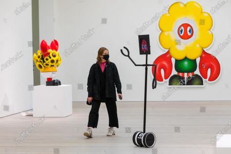 Stock Photo of A woman wearing a mask walks past robots and exhibits at the press preview of Philip Colbert's Coronavirus lockdown inspired exhibition, 'Lobsteropolis' at the Saatchi gallery in London, Britain, 29 October 2020.  Visitors can attend in person but also connect to a robot via a smartphone or computer to view the exhibition remotely. Born from isolation and the severance of human connection through social distancing, Colbert wanted to create a lockdown-proof concept, which aims to transport visitors through an odyssey of unseen large-scale paintings and sculptures.