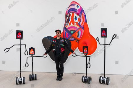 Artist Philip Colbert poses with robots at the press preview of his Coronavirus lockdown inspired exhibition,  'Lobsteropolis' at the Saatchi gallery in London, Britain, 29 October 2020.  Visitors can attend in person but also connect to a robot via a smartphone or computer to view the exhibition remotely. Born from isolation and the severance of human connection through social distancing, Colbert wanted to create a lockdown-proof concept, which aims to transport visitors through an odyssey of unseen large-scale paintings and sculptures.