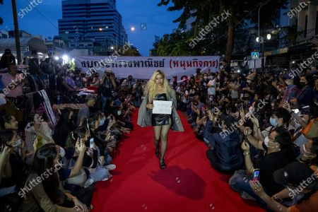"Pro-democracy protesters perform on a mock ""red carpet"" fashion show billed as a sort of counterpoint to a fashion show being held by one of the monarchy's princesses nearby in Bangkok, Thailand, . The protesters continued to gather Thursday, led by their three main demands of Prime Minister Prayuth Chan-ocha's resignation, changes to a constitution that was drafted under military rule and reforms to the constitutional monarchy. Sign reads ""Winter Collection"" upside-down"