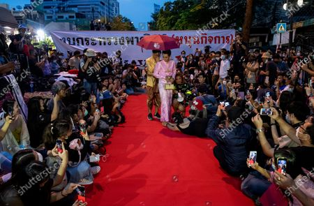 "Pro-democracy protesters perform on a mock ""red carpet"" fashion show billed as a sort of counterpoint to a fashion show being held by one of the monarchy's princesses nearby in Bangkok, Thailand, . The protesters continued to gather Thursday, led by their three main demands of Prime Minister Prayuth Chan-ocha's resignation, changes to a constitution that was drafted under military rule and reforms to the constitutional monarchy"