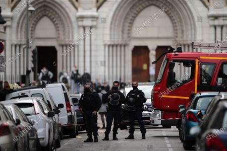 Police officers stand guard near Notre Dame church in Nice, southern France, . An attacker armed with a knife killed at least three people at a church in the Mediterranean city of Nice, prompting the prime minister to announce that France was raising its security alert status to the highest level. It was the third attack in two months in France amid a growing furor in the Muslim world over caricatures of the Prophet Muhammad that were re-published by the satirical newspaper Charlie Hebdo