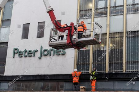 Workmen install Christmas lights to the exterior of Peter Jones department store in Sloane Square. The store is part of the John Lewis group whose flagship store in Oxford Street has been granted permission to turn half of the building into offices as the company undergoes a restructuring plan to stem a downturn in business performance suffered during the ongoing coronavirus pandemic. In addition, staff will not be paid their annual bonus for the first time since 1953.的庫存圖像