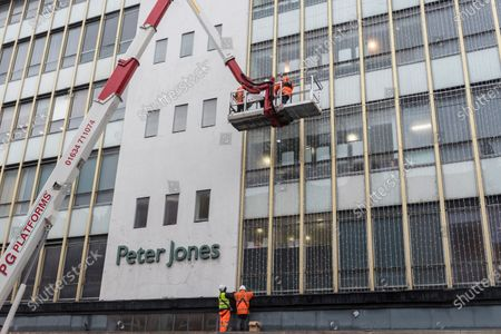 Workmen install Christmas lights to the exterior of Peter Jones department store in Sloane Square. The store is part of the John Lewis group whose flagship store in Oxford Street has been granted permission to turn half of the building into offices as the company undergoes a restructuring plan to stem a downturn in business performance suffered during the ongoing coronavirus pandemic. In addition, staff will not be paid their annual bonus for the first time since 1953.的庫存圖片