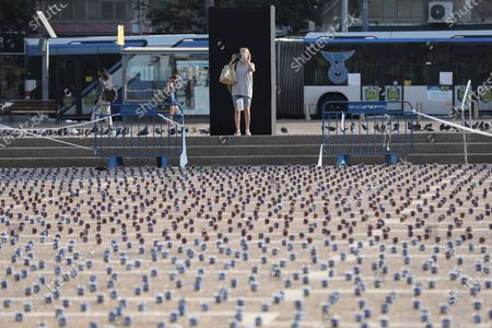 Stock Photo of A women takes pictures of 25,000 memorial candles for the 25th anniversary of the assassination of the late Israeli PM, Yitzhak Rabin in Rabin Square, Tel Aviv, Israel, 29 October 2020. Rabin received the Nobel Prize for Peace in 1994 along with his Foreign Minister Shimon Peres and Palestine Liberation Organization leader Yasser Arafat, for their efforts towards peace. He was the fifth Prime Minister of Israel, serving two terms in office, 1974-77, and 1992 until his assassination in 1995. Rabin was fatally shot after attending a peace rally held in Tel Aviv's Kings Square by a far-right Jewish law student, on 04 November 1995.