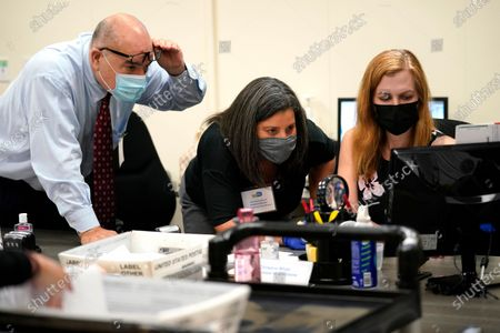 Miami-Dade County Supervisor of Elections Christina White, right, examines signatures on vote-by-mail ballots with members of the Canvassing Board Judge Raul Cuervo, left, and Judge Betsy Alvarez-Zane, center, at the Miami-Dade County Board of Elections in Doral, Fla. Florida will never experience another election meltdown exactly like the one that made the state an international laughingstock in 2000, when after a five-week recount and court battle George W. Bush edged Al Gore and won the presidency. State leaders eliminated computer punchcard ballots, implemented statewide recount laws and made it easy to cast and process ballots before Election Day