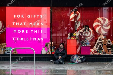 A beggar sits under the optimiostic gifts message -  Peter Jones, part of the John Lewis Partnership, prepares for Christmas as the Coronavirus restrictions begin to increase again. Traditional lights are hung from the facade and window displays mostly relate to Christmas.