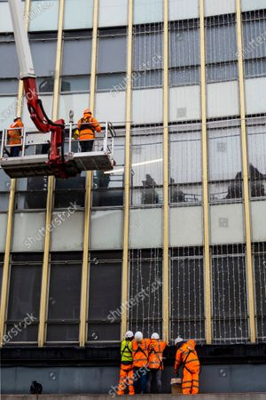 Workmen hang the strings of lights - Peter Jones, part of the John Lewis Partnership, prepares for Christmas as the Coronavirus restrictions begin to increase again. Traditional lights are hung from the facade and window displays mostly relate to Christmas.