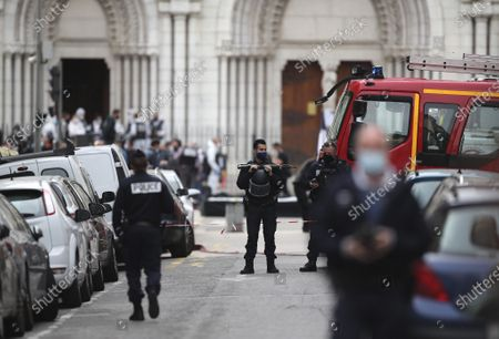 Police officers stand guard near the Notre Dame church in Nice, southern France, after a knife attack took place on . An attacker armed with a knife killed at least three people at a church in the Mediterranean city of Nice, prompting the prime minister to announce that France was raising its security alert status to the highest level