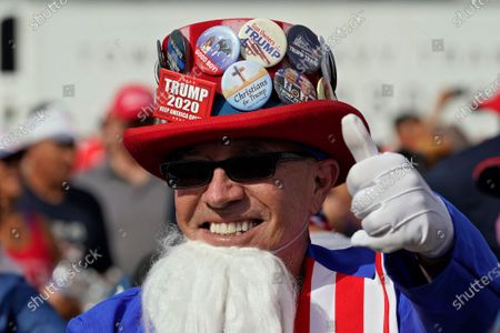 Will Enderly, dresssed as Uncle Sam, gestures to friends before a campaign rally by President Donald Trump, in Tampa, Fla