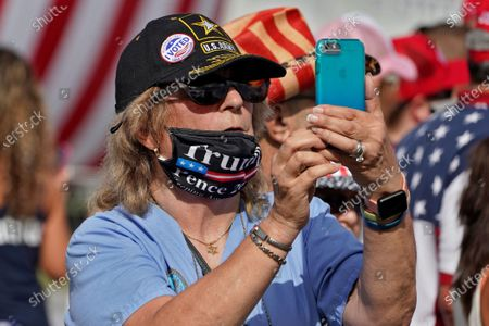 President Donald Trump supporter takes photos of the crowd before a campaign rally by the president, in Tampa, Fla