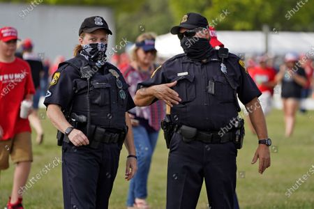 Tampa, Fla., police officers wearing protective equipment as they survey the crowd before a campaign rally by President Donald Trump, in Tampa, Fla