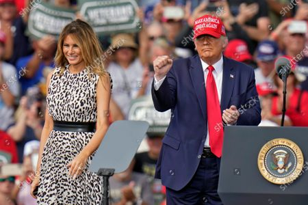 President Donald Trump pumps his fist as first lady Melania Trump smiles at supporters after a campaign rally, in Tampa, Fla
